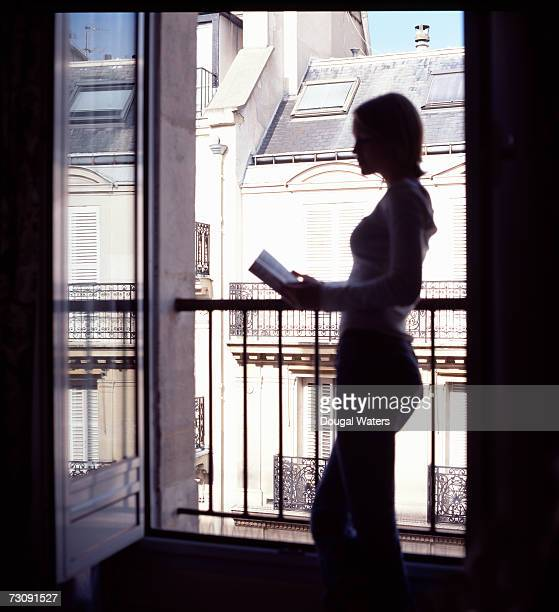 Young woman reading at balcony in apartment, profile (back lit)