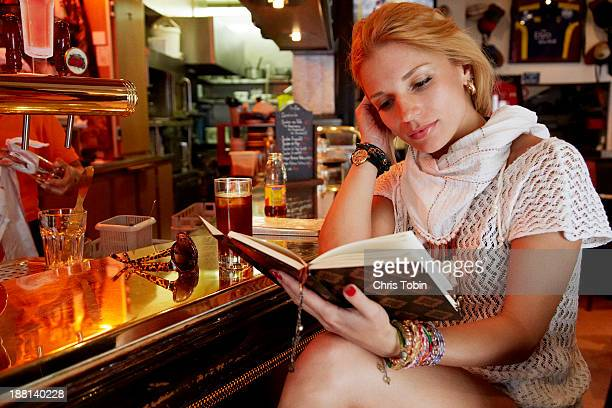 Young woman reading at bar