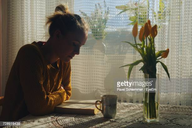 Young Woman Reading Book Against Window While Sitting At Table