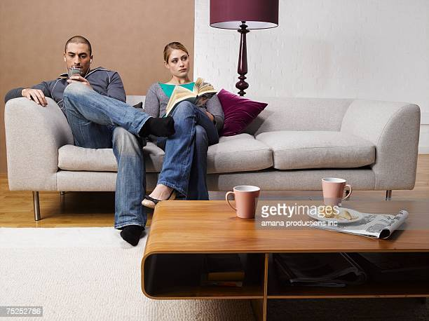 Young woman reading book and young man listening to MP3 player on sofa