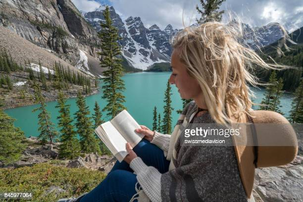 Young woman reading book at mountain lake