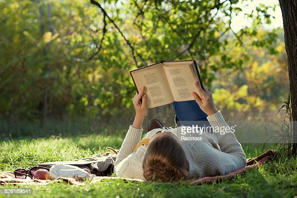 Young woman reading book at the park