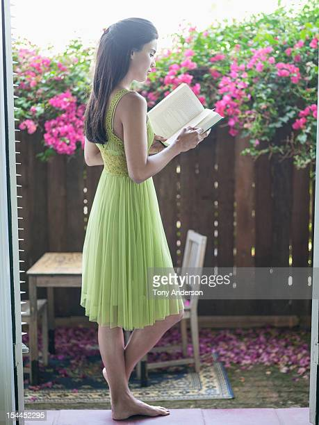 Young woman reading book in back yard