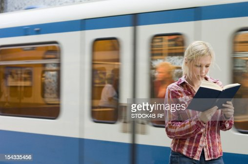 Young woman reading book in front of passing subway