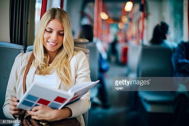 Junge Frau liest ein Buch im öffentlichen Verkehrsmittel.