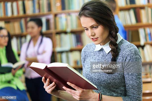 Young woman reading book in the library