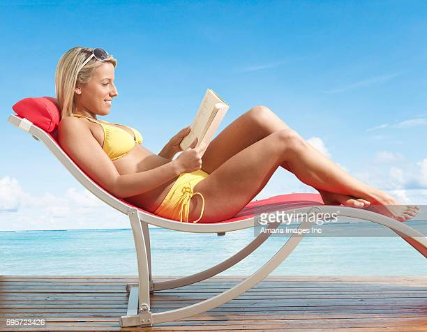 Young Woman Reading Book on Lounge Chair