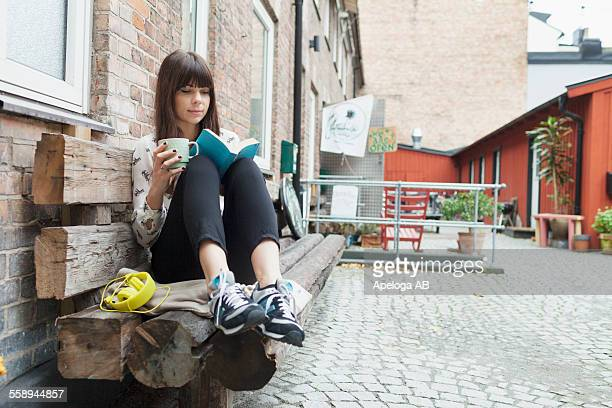 Young woman reading book while holding coffee cup at cafe backyard