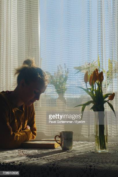 Young Woman Reading Book While Sitting At Table In House