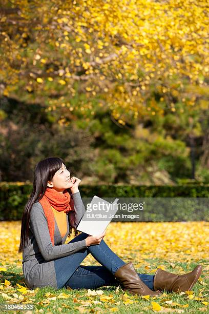Young woman reading books in beautiful autumn day