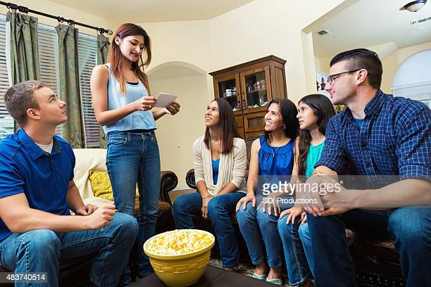 Young woman reading card during game of charades with friends