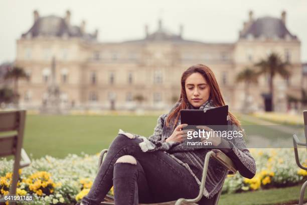 Young woman reading e-book outside