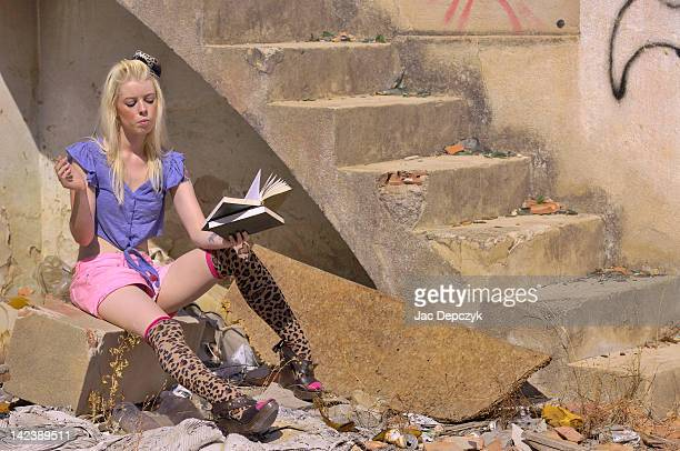 Young woman reading in a derelict house