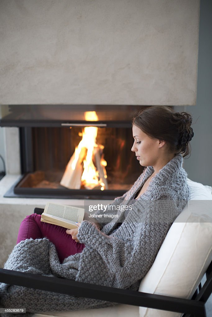 Young woman reading in front of fireplace