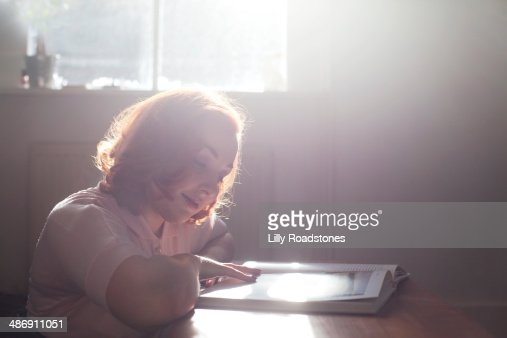 Young woman reading in her home : Stock Photo