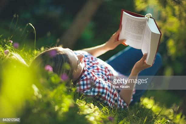 Giovane donna leggendo nel giardino