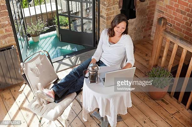 Junge Frau liest laptop beim Kaffee am Morgen loft-apartment