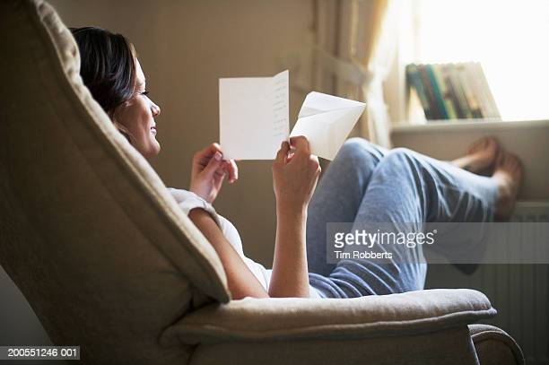 Young woman reading letter and smiling
