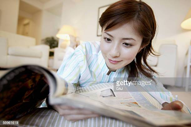 Young Woman Reading Magazine and Lying Down