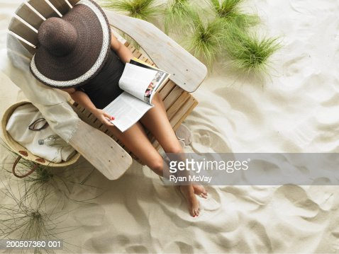 Young woman reading magazine on Adirondack chair, overhead view : Stock Photo