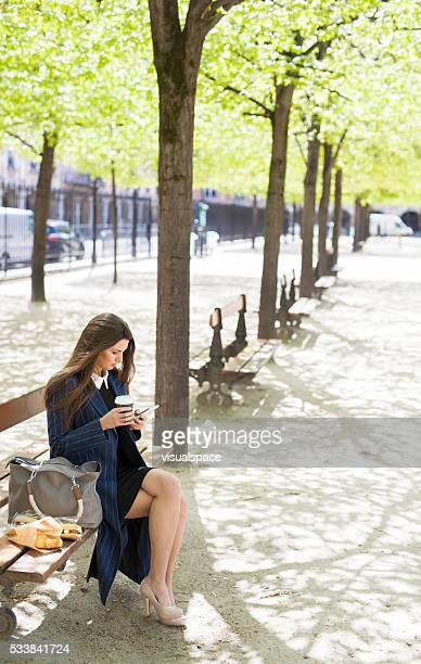 Young Woman Reading News on Smartphone in a Park