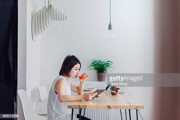 Young woman reading news on tablet whilst having breakfast