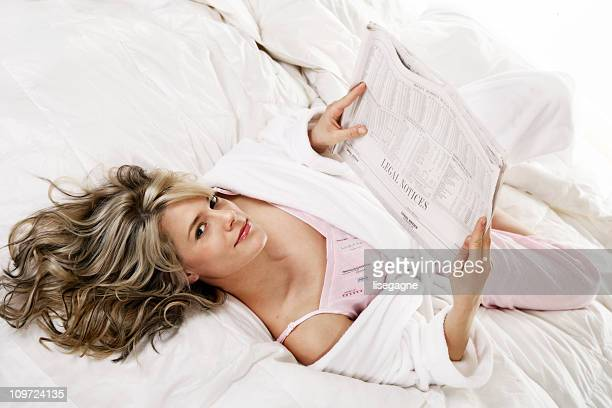 Young Woman Reading Newspaper in Bed