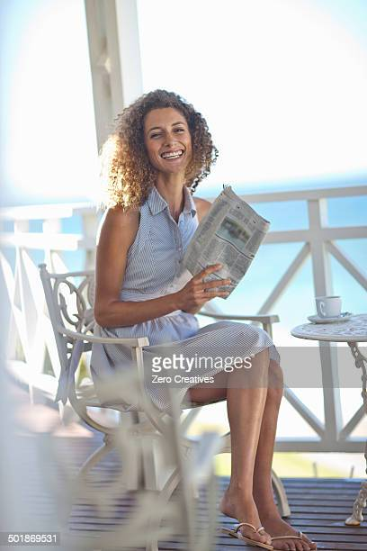 Young woman reading newspaper on beach house balcony