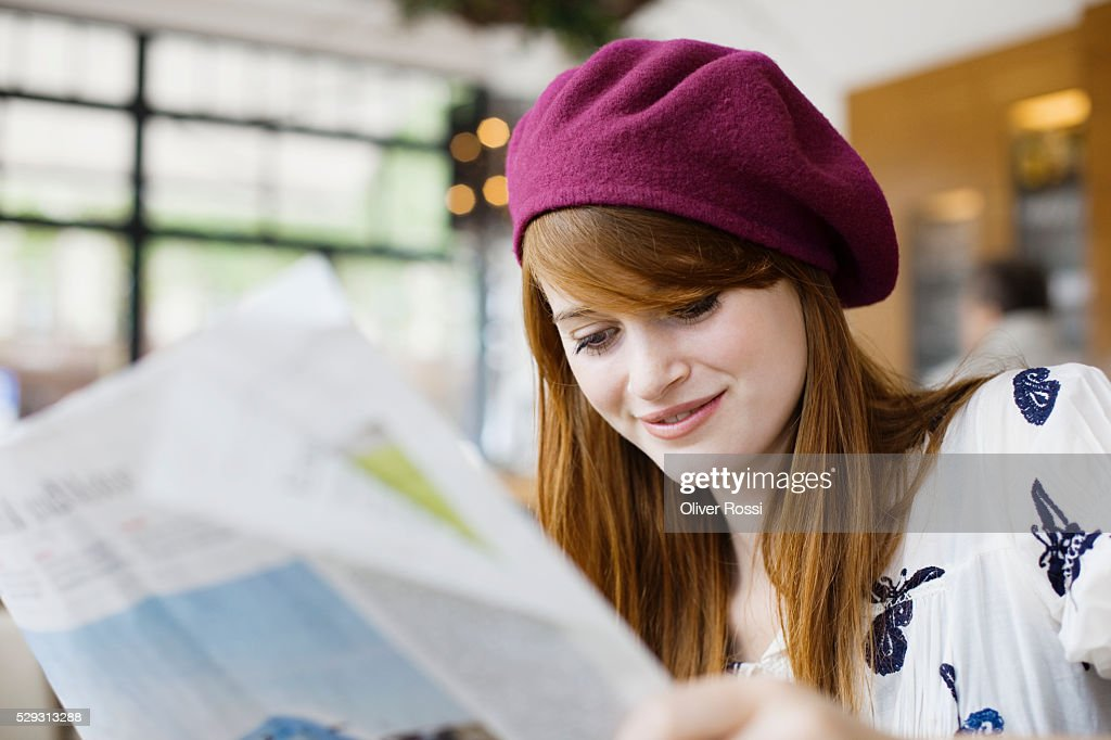 Young woman reading newspaper : Stock Photo