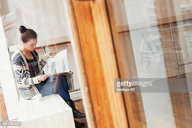 Young woman reading newspaper while sitting in coffee shop