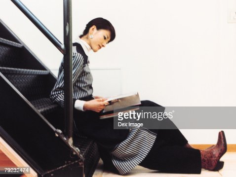 Young woman reading on stairs : Stock Photo