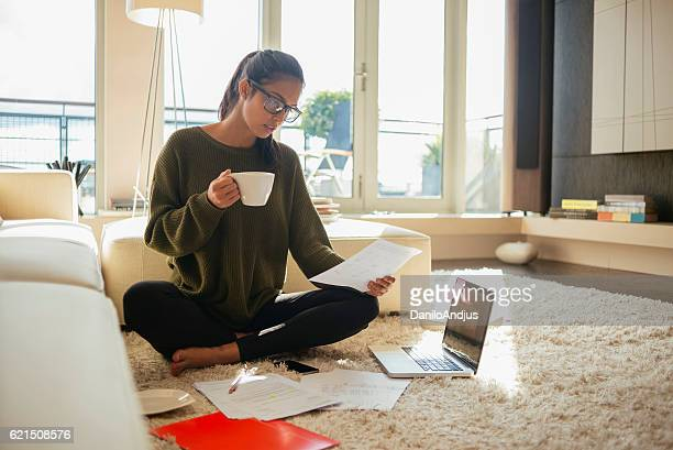 young woman reading paperwork in her living room,
