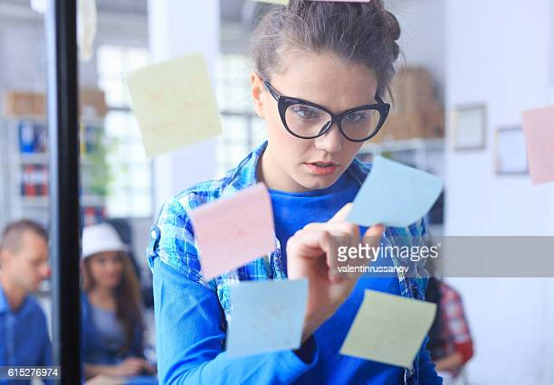 Young woman reading post-it notes from glass wall
