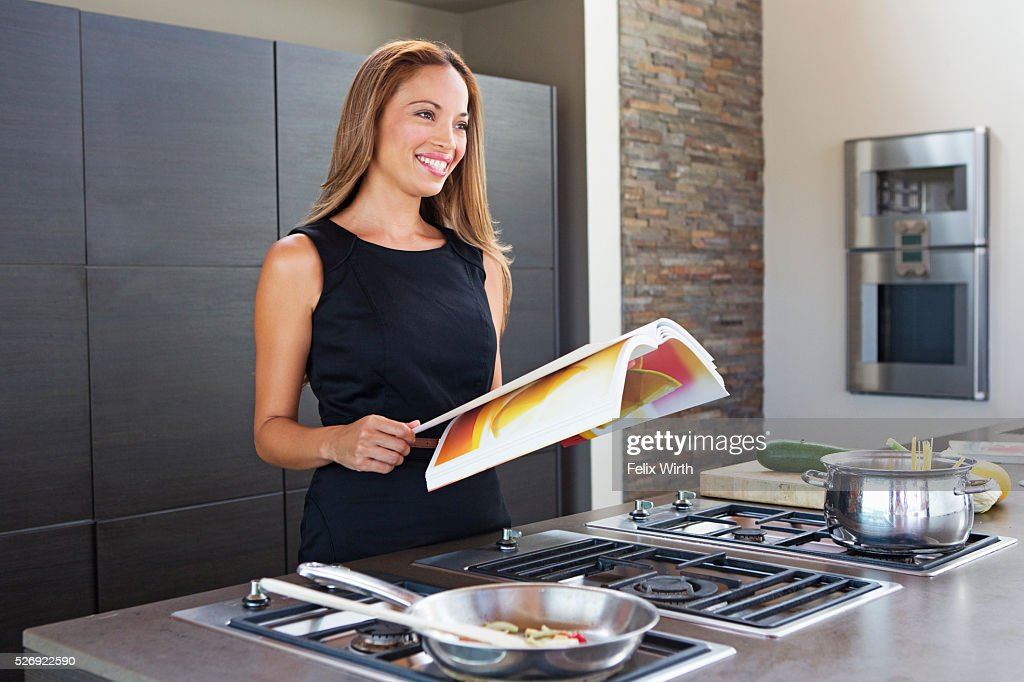 Young woman reading while cooking dinner : ストックフォト