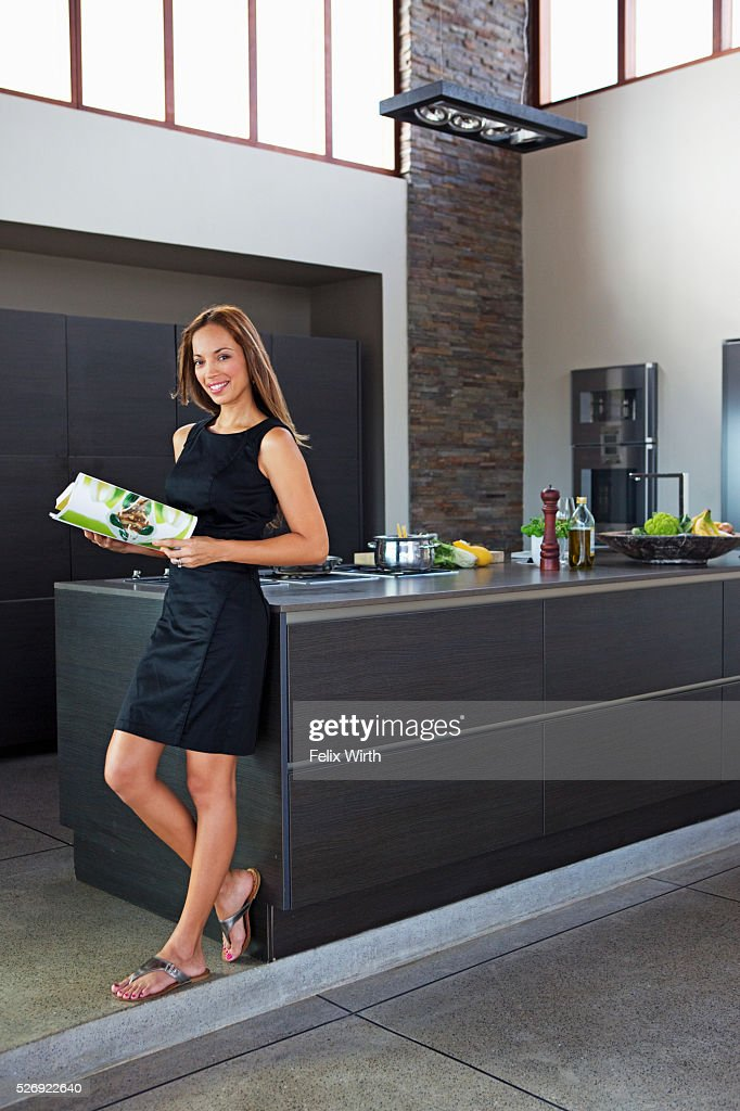 Young woman reading while cooking dinner : Stockfoto