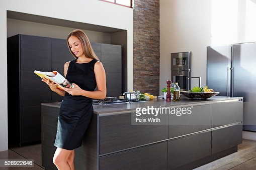 Young woman reading while cooking dinner : Stock Photo
