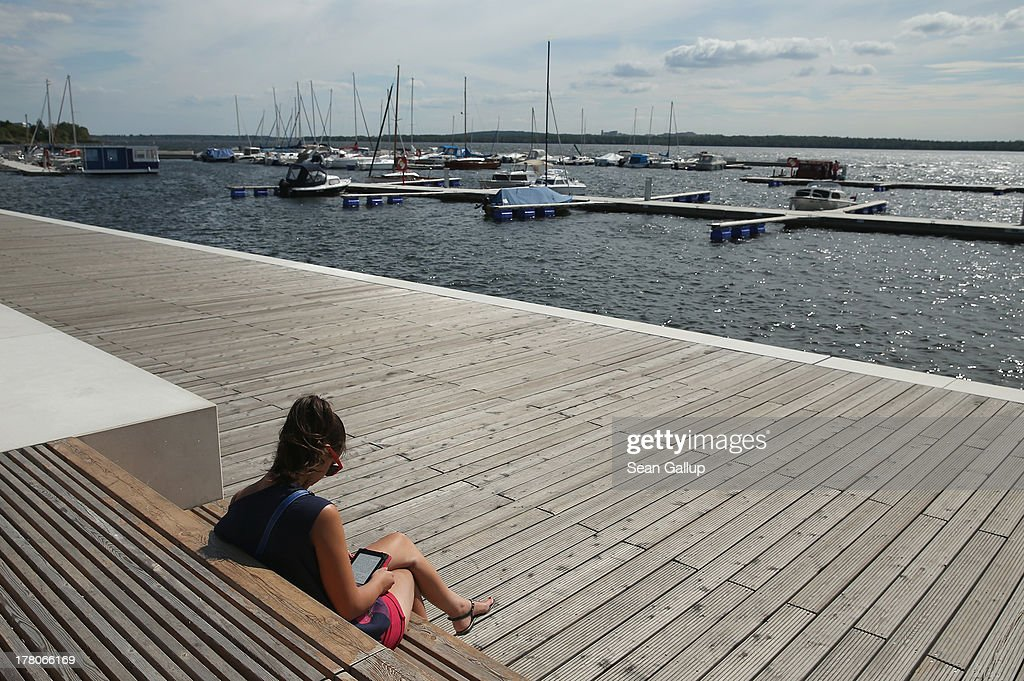 A young woman reads a book along the boardwalk at the marina of artifiticial Senftenberger See lake on August 26, 2013 in Senftenberg, Germany. Senftenberger See was once an open-pit lignite coal mine flooded after it shut down in the late 1960s, and today it is popular among tourists, windsurfers and fishermen. In a development project initiated by state government, other nearby former open-pit mines that once evoked a lunar landscape are being turned into lakes in a long-term rejuvenation effort that is also intended to make the area a viable tourist destination. Mineral residue from the mines, however, is proving a difficult stumbling block that is making many of the new lakes too acidic to sustain marine life in the short term.