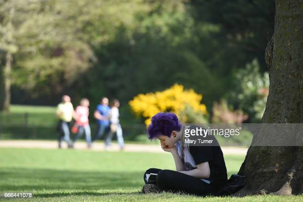 A young woman reads a book in the shade on the hottest day of the year so far in St James's Park on April 9 2017 in London England Temperatures are...