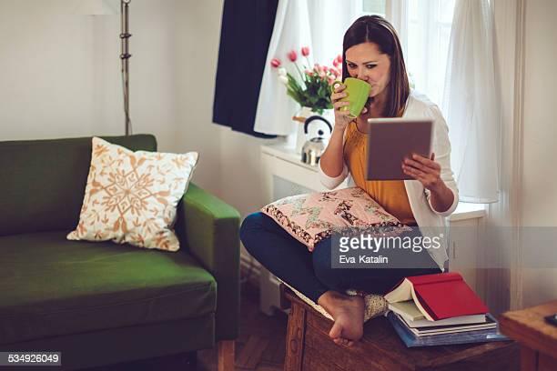 若い女性の読み取りタブレットやお飲物、コーヒーを自宅に