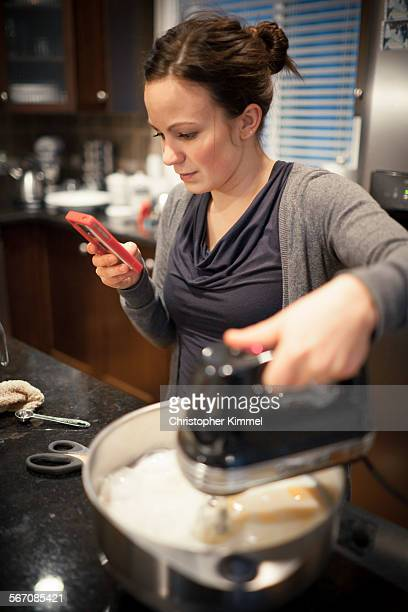 A young woman reads from her smartphone while cooking in the kitchen.