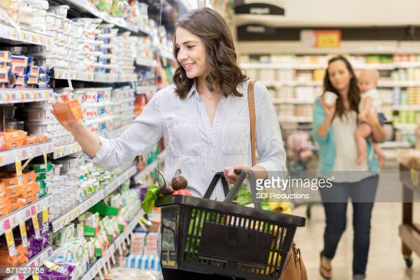 Young woman reads nutrition on a package of cheese in grocery store
