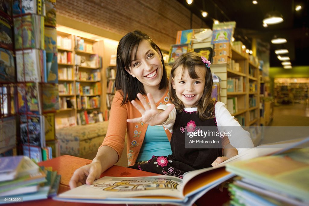 Young woman reads with child : Stock Photo