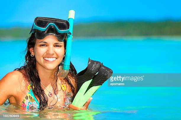 Young woman ready for snorkeling in a tropical turquoise beach