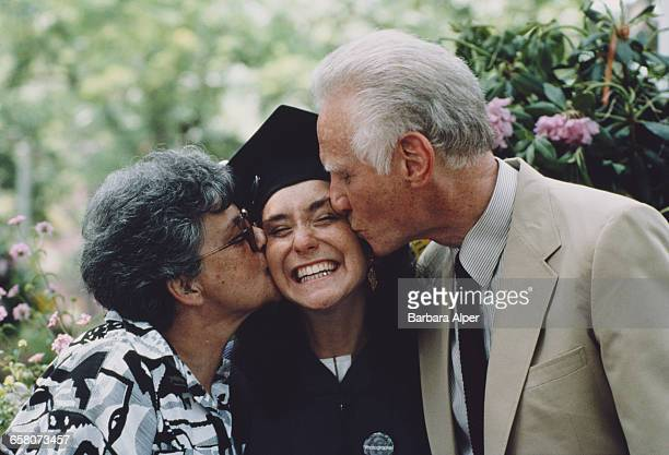 A young woman receives the congratulations of her family on graduation day at New York University New York City June 1986