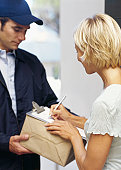 young woman receiving a package from a delivery man