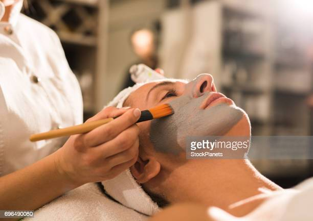 Young woman receiving facial mask during cosmetic treatment at beauty salon.