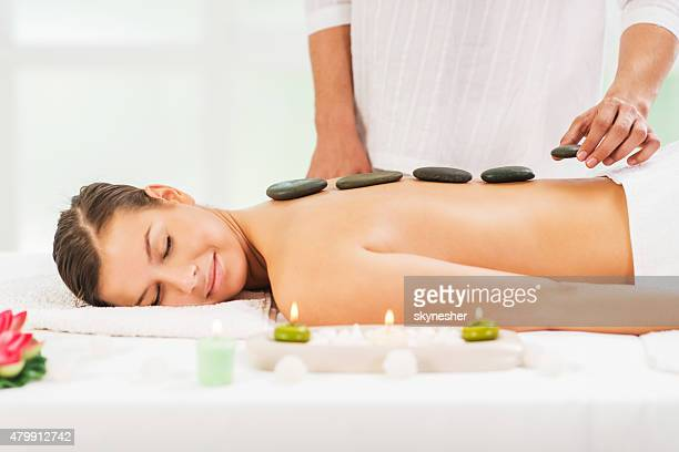Young woman receiving hot stone therapy treatment.