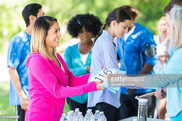 Junge Frau empfangende Nummer und t-shirt nach der Anmeldung für das Rennen