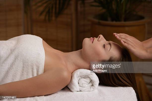 Young woman receiving reiki massage