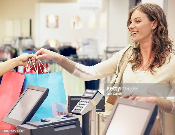 Young woman receiving shopping bags over counter in shop, smiling